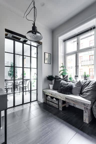 This is a picturesque Scandinavian-Style foyer with glass French doors leading to dark-tiled floors. These floors are brightened up by a large window embedded into the white wall adjacent to the doors. This window has a wooden bench beneath it with pillows and a shoe rack crate beneath.