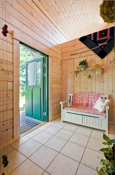 This is a charming foyer that welcomes the guests with a wooden green main door that has a glass window attached to it. This main entry leads to a room with bare wooden walls paired with a quaint cushioned wooden bench that matches the white-tiled flooring.