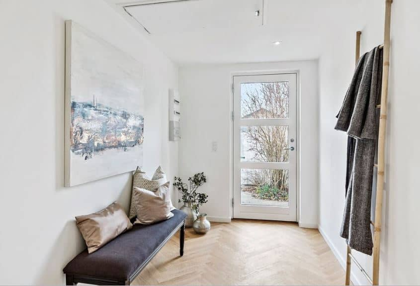 This Scandinavian-Style foyer's main door is a simple white door with three glass panels that serve as a window to this enclosed white-walled space. The hardwood flooring contrasts the white ceiling and complemented by a dark wooden cushioned bench.