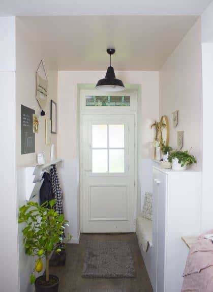 This small and white Scandinavian-Style foyer has a built-in wooden bench on one side that blends with the white wall. On the other wall is a wall-mounted coat and hat rack as well as a mailbox topped with wall-mounted artworks that bring warmth.