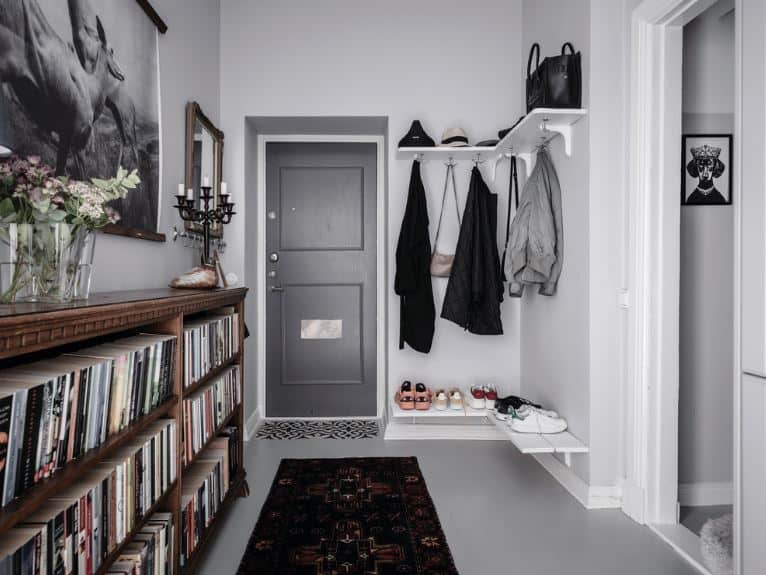 Upon entrance of the gray wooden door, the guests are welcomed by a long waist-high bookshelf on one side that also serves as a high console table. Across from it are the wall-mounted white shoe rack and coat rack blending with the white wall.