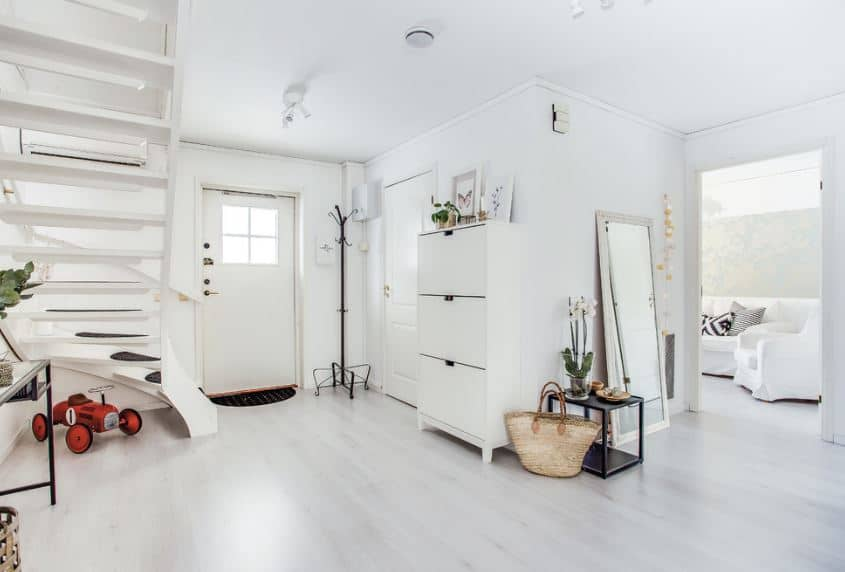 The white main door has a built-in window of frosted glass that brings in natural light to the white walls and white ceiling where a modern semi-flush light is mounted. Beside the door is a standing dark iron coat and hat rack across the white spiral stairs.
