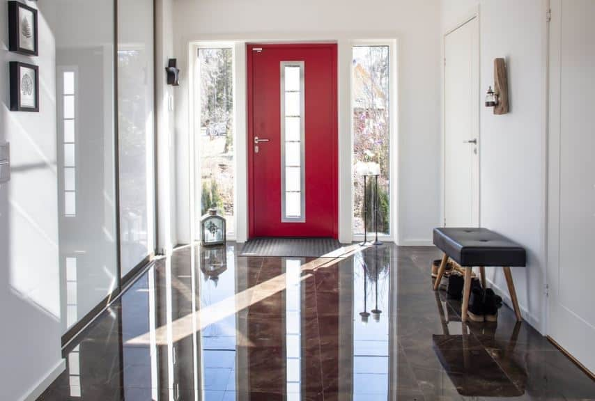 This Scandinavian-Style foyer has a sleek and dark marble flooring that reflects the natural light coming in from the side lights flanking the dramatic red door. This door contrasts the white walls and white ceiling. On the side is a black leather upholstered bench.