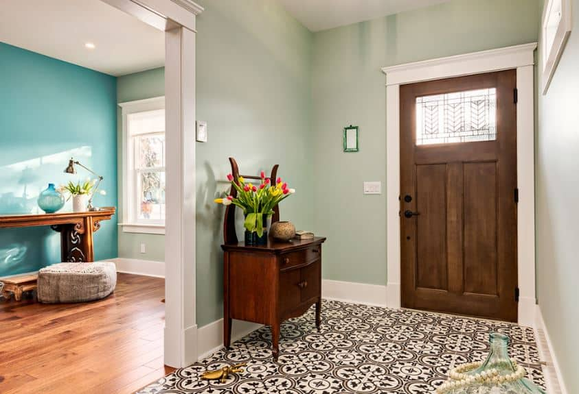 The wooden console table on one side has built-in drawers and cabinets and matches with the wooden main door. This is a good contrast for the light green walls and a white ceiling that is ultimately contrasted by the intricate patterns of the tiled-flooring.