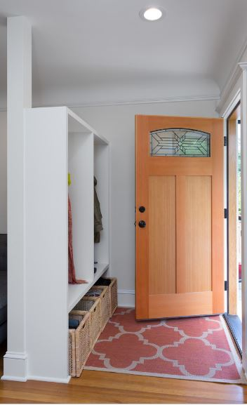 The hardwood flooring of this small foyer is covered by a reddish patterned area rug to mark its space and at the same time protect the floor from the outside dirt. As you enter, you are welcomed by a white wooden structure that serves as a coat rack and shoe rack.