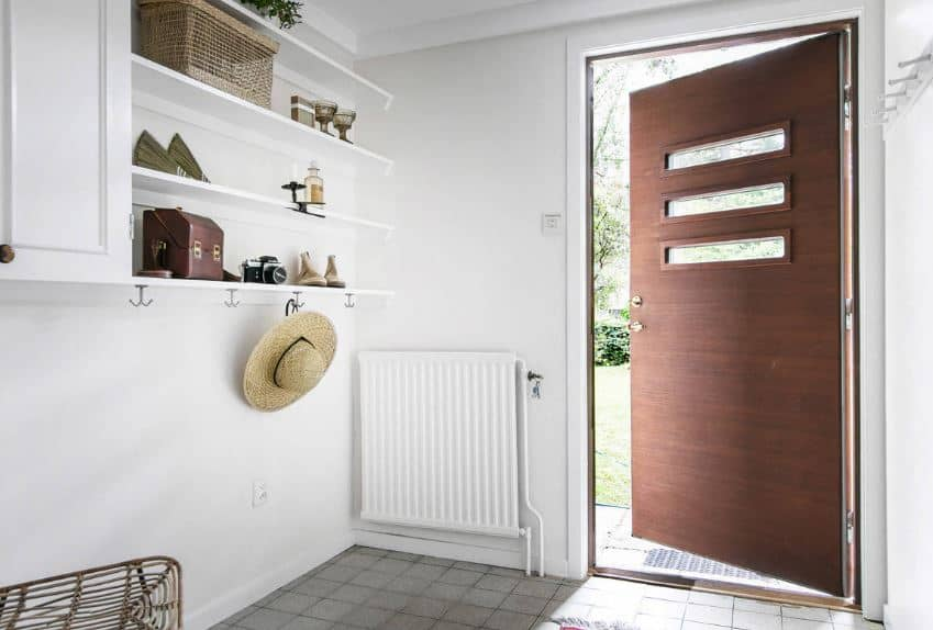 The wooden main door has a design of three stripes of glass viewing slots. Upon entry, there is a white radiator on the sidewall to provide warmth to those entering. The wall adjacent to this has wall-mounted shelves and cabinets that double as coat racks.