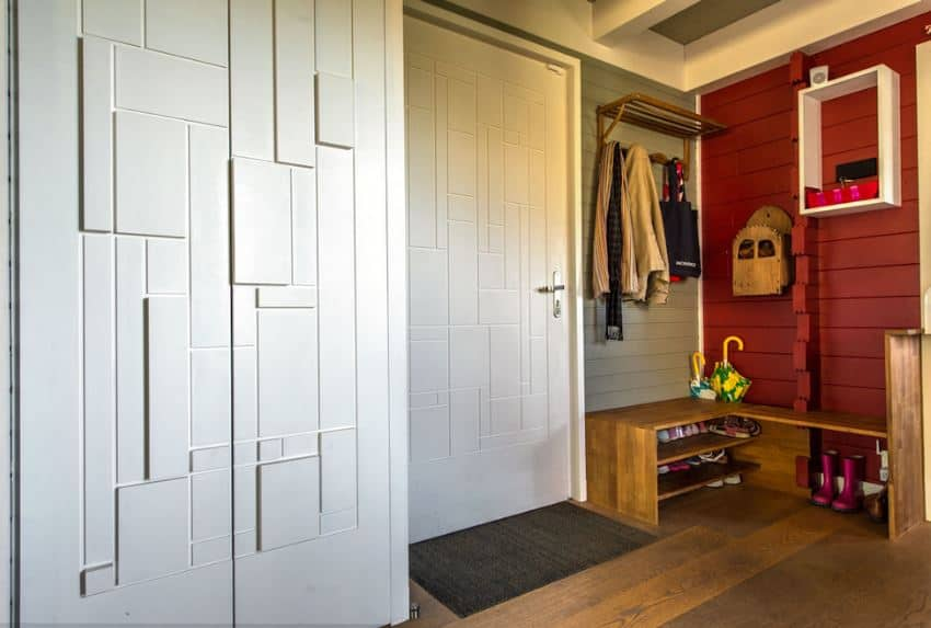 This is a Scandinavian-Style foyer that also doubles as a mudroom with its L-shaped wooden bench that has shoe racks beneath it and coat racks mounted on the wall above. The wall adjacent to the door is painted red and contrasted with a white floating shelf.