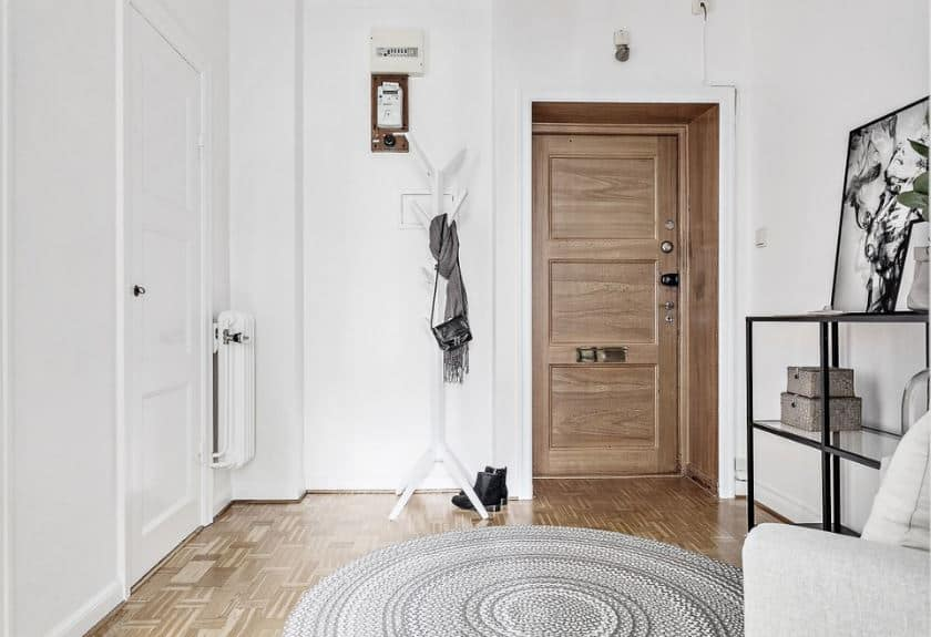 The wooden main door is sunken into the white walls and pairs well with the hardwood flooring that has a circular gray patterned area rug. Beside the doorway is a white standing coat and hat rack that blends with the white wall.