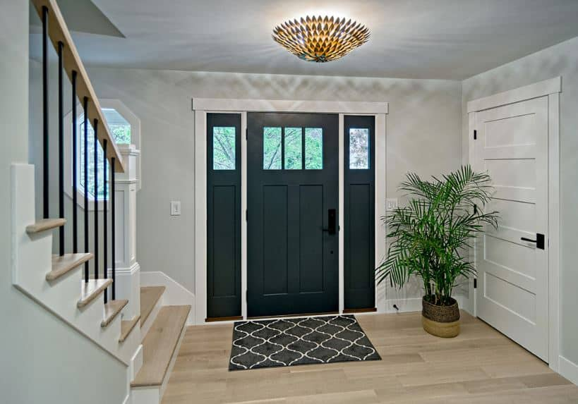 The hardwood flooring is topped with a dark patterned area rug that serves as a welcome mat for the guests. This pairs well with the dark wooden door with matching side lights. This room is illuminated by a gorgeous flush light mounted on the white ceiling.