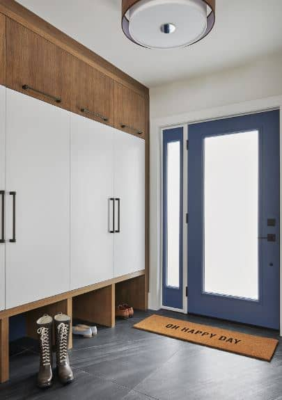 Upon entry of the frosted glass door with blue frames, the guests are greeted by a delightful brown welcome mat over the dark gray tiles of the floor. There is a large wooden structure on one side that houses cabinets and the shoe racks beneath it.