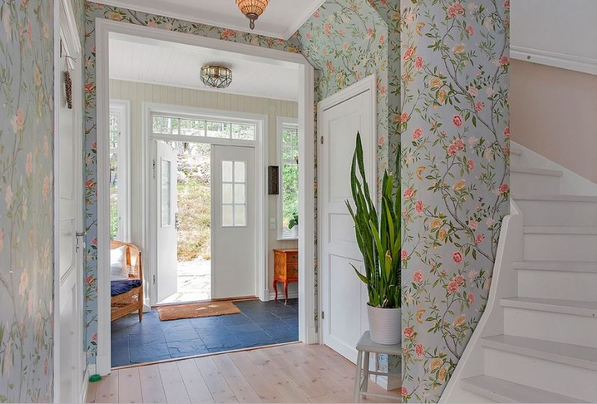 This is a beautiful foyer that eases the guests into the chic flowery wallpapers of the main hall. The foyer has blue textured stone tiles for the floor and white double doors on the main door paired with a narrow transom window above.