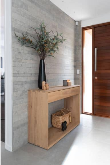 The redwood door has a striped design on it made from the wooden planks. This pattern is mirrored on the gray walls adjacent to it. This gray background makes the wooden console table stand out with its adornment of a rustic basket beneath and a black flower vase on top.