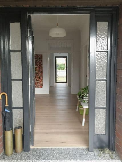 This Scandinavian-Style foyer has a dark gray wooden door with similar-toned side lights that have frosted glass windows. This lovely main door opens to hardwood flooring paired with a wooden bench on one side illuminated by a white pendant light.