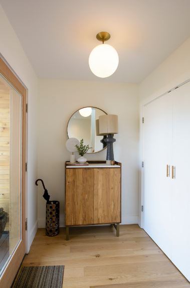 There is a warm spherical semi-flush light mounted on the white ceiling that shines yellow light down on the hardwood flooring topped with a patterned area rug serving as a doormat. There is a wooden cabinet on the side topped with a circular wall-mounted mirror and lamp.