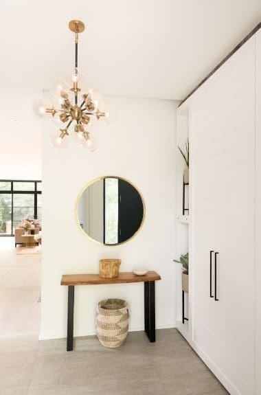 The intricate modern brass chandelier hanging from the white ceiling is a nice touch of elegance on the white monotony of the white walls and cabinets. There is a simple wood-topped console table on the side of the white wall adorned with a wall-mounted circular mirror.