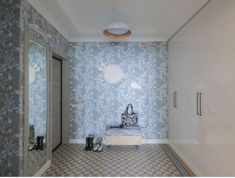 This is a charming Scandinavian-Style foyer that is complemented by the chic flowery wallpaper covering the walls. This contrasts with the white ceiling and the white cabinets. The floor is a whole different story with its beige patterned tiles.