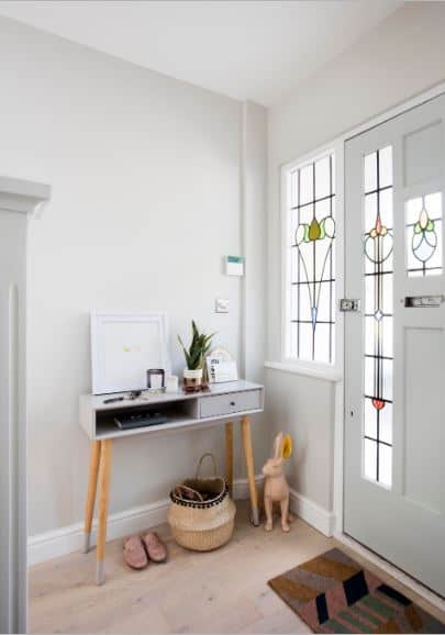 This simple foyer has a few touches of whimsy with its beige rabbit statuette and colorful welcome mat that matches the splashes of color on the stained glass panels of the door and its side lights. These elements stand out against the plain white background of walls and ceiling.