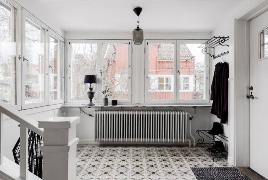 This is a lovely and cozy foyer with rows of windows surrounding it bringing in natural light from the suburban surrounding. Warmth is brought by the radiator by the shoe rack and coat rack beside the white door. The patterned floor tiles complement the black and white theme of this foyer.