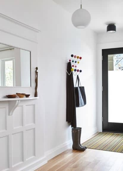 This is a bright and white Scandinavian-Style foyer with its white walls and white ceiling illuminated by the glass main door and the white spherical pendant light. The colorful contrast comes from the welcome mat and colorful beads of the coat rack.