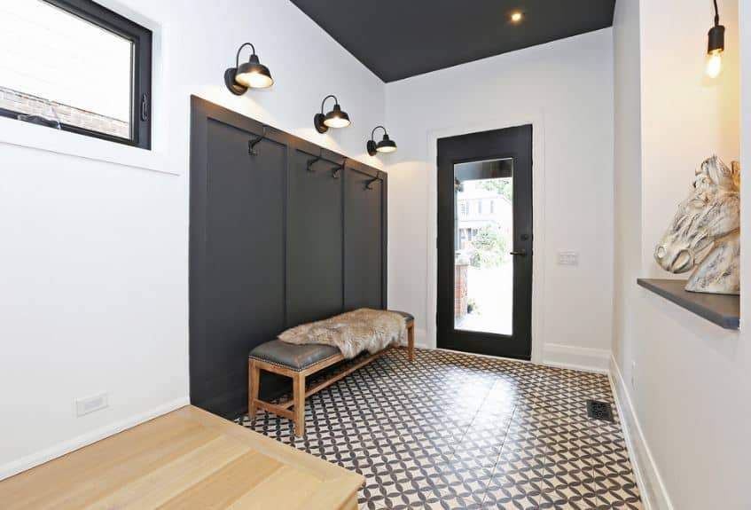 The sidewall of this foyer has a black wood finish with wall-mounted hooks for coats and hats. This is topped by wall-mounted lamps shining yellow light on the long cushioned bench below. The glass door illuminates the intricate patterns of the floor tiles.