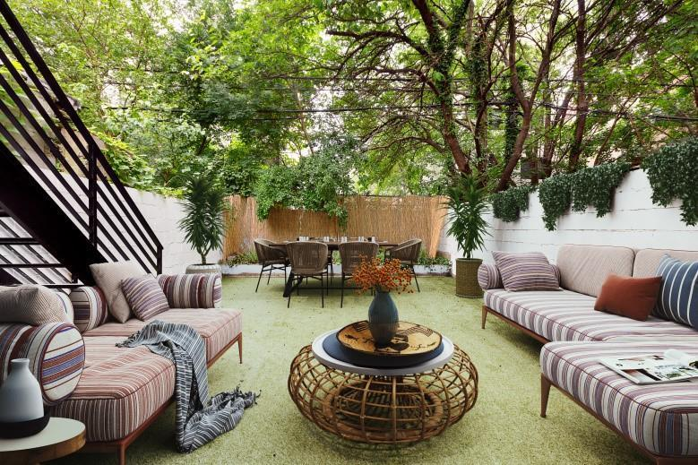 This relaxing scenery of Scandinavian-Style landscaping has a couple of large cushioned couches on either side of a rustic wooden coffee table. On the other end of the manicured grass lawn is an outdoor dining area with rustic chairs and flanked with potted plants.