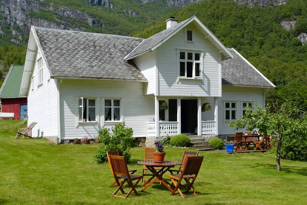 The white exteriors of the house is a charming background to this Scandinavian-Style landscape of the well-maintained grassy front yard. There is an outdoor dining area with wooden folding chairs surrounding a circular table of the same make besides a medium-sized tree.