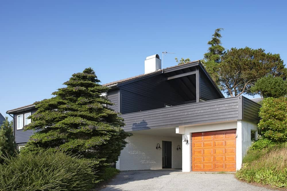 The exterior of the house has a simple and modern design with straight lines and a modern color palette. This theme is perfectly contrasted by a Scandinavian-Style landscape of overgrown shrubs and tall trees that make it seem like the house is in a jungle.