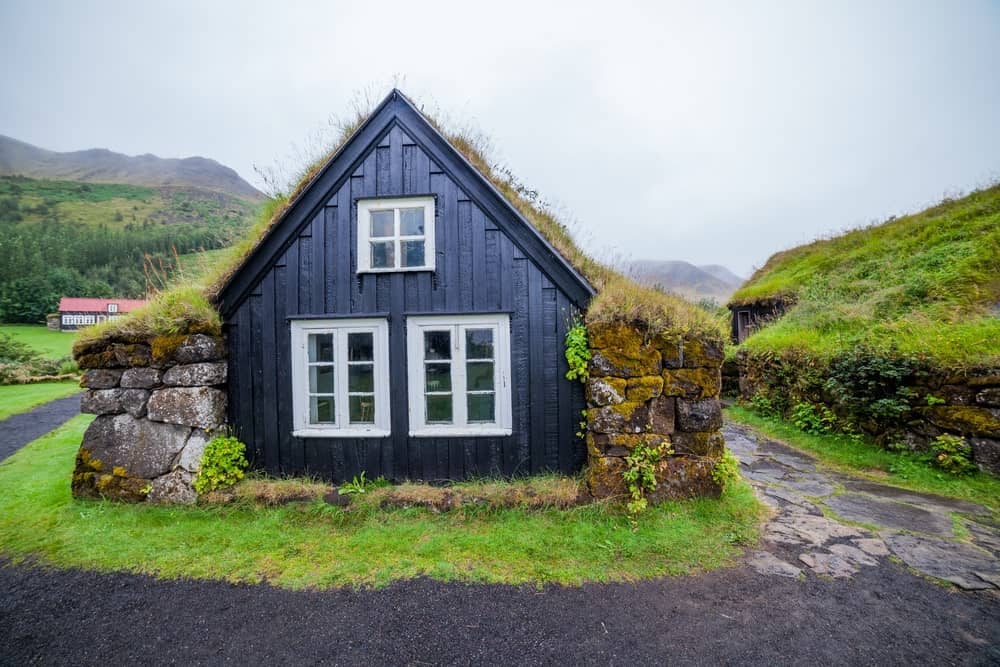 This traditional house was probably the inspiration behind the hobbit homes in fictionary tales. The wooden house of dark gray hue is flanked with a couple of ancient-looking stone columns with carpets of grass on top extending to the rooftops of the house.