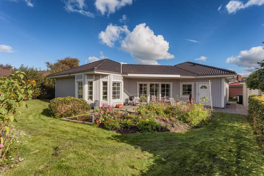 This is a Scandinavian-Style landscape dominating the backyard of this house with a proper carpet of grass that surrounds a miniature garden at the back of the house. This garden is filled with colorful flowers that match the hedges surrounding the lawn.