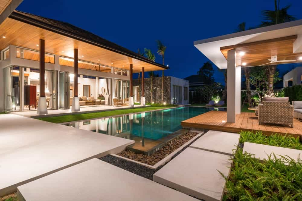 This is a modern and cozy Scandinavian-Style landscape that exudes an aura of luxury and elegance. It has a rectangular infinity pool that is surrounded by the straight lines of the stone walkways. These walkways are paired with small ferns to emphasize their light color.