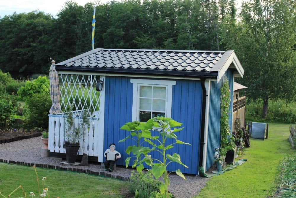 This small and simple blue house integrates itself with the surrounding Scandinavian-Style landscape with its well-manicured carpets of grass next to graveled pathways. There is also a creeping plant climbing up one side of the house's blue wall.