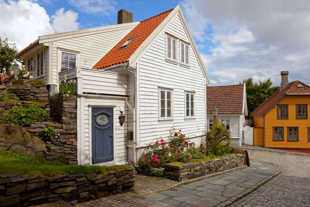This Scandinavian-Style landscape has terraced ledges made of stone. The lowest ones are flanking the main entryway and elevate only about a foot from the sidewalk. The highest stone terrace is higher than the main door providing support for the wooden structure.