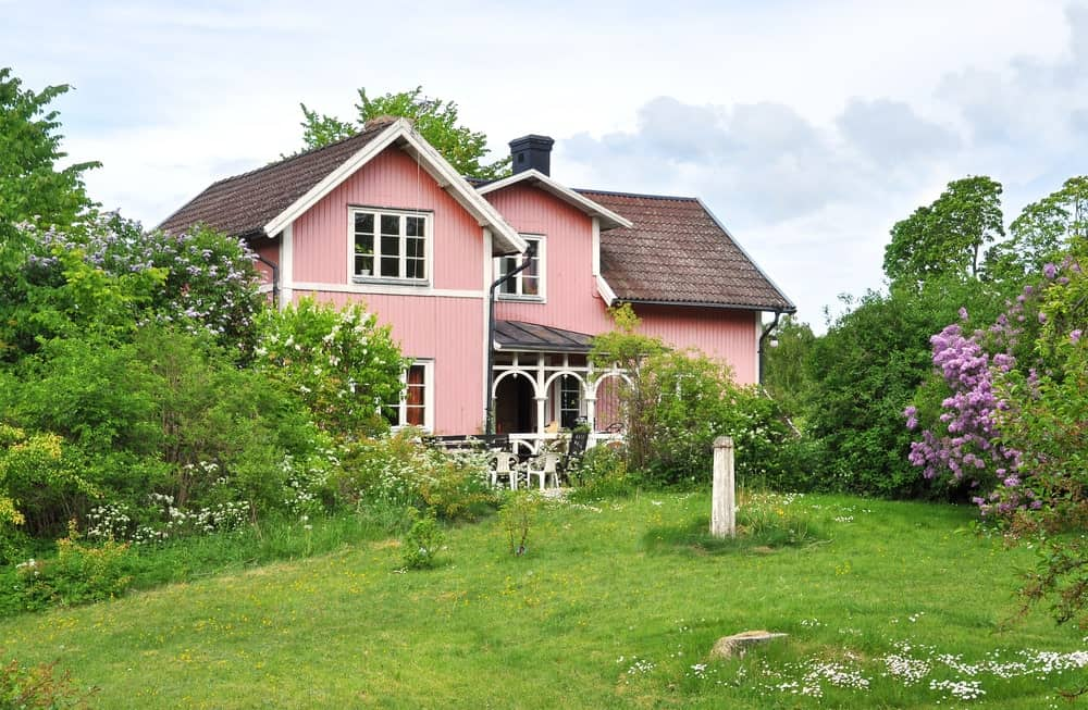 The landscape that is filled spring elements perfectly suits the pink facade of the house exterior. It has various flowering plants and shrubbery that flanked the entrance to the house as well as medium-sized trees that frame the charming area.