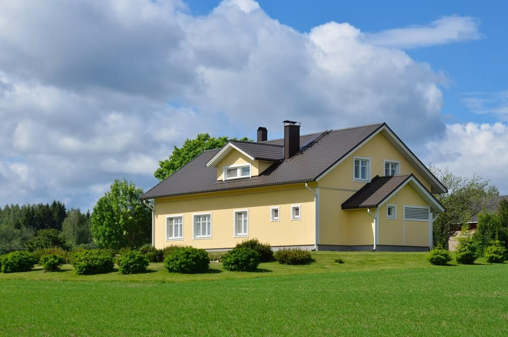 This Scandinavian-Style landscape has various shrubs that are well-manicured to look like clouds that surround the house against a background of straight grassy lawns. This is a perfect match for the cloudy skies over the lovely beige house.