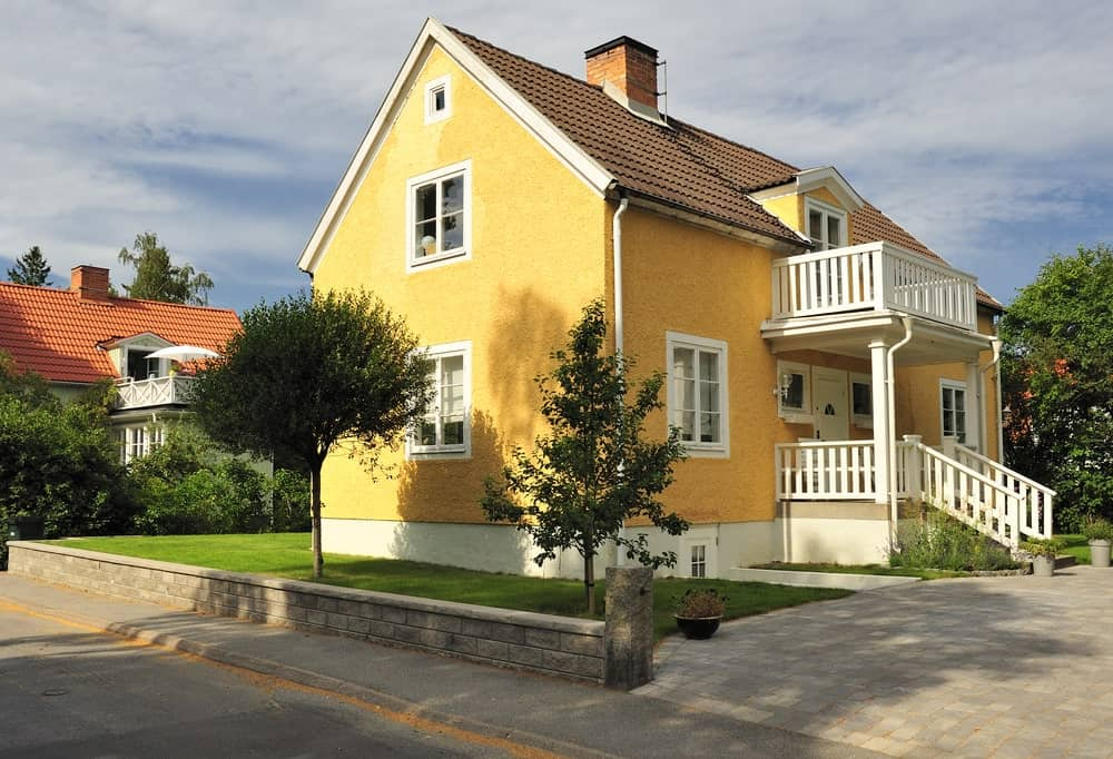 There is a low stone wall separating the grassy lawn of the beige house and the sidewalk made of cement that has a brick wall design on the side and ends with a small column by the driveway. The driveway is also made of stone bricks that are slightly lighter than the wall.