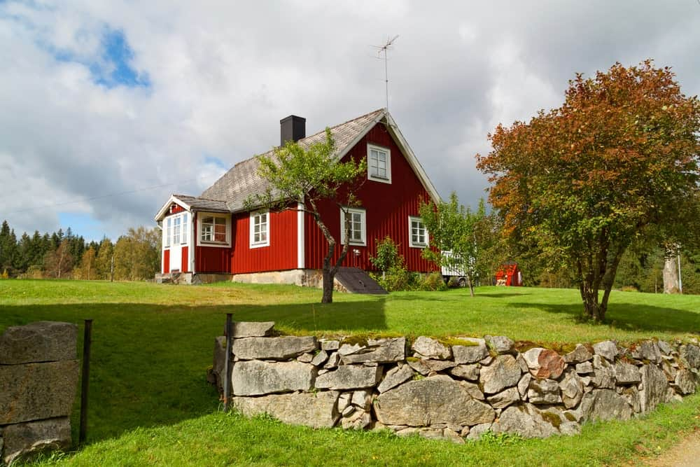 The wide and spacious grassy lawn of the red house provides a nice contrast of green on red that makes the lawn seem bigger. It is surrounded by a low wall of various sizes of stone assembled to form a ledge for the sloping lawn dotted with medium-sized trees.