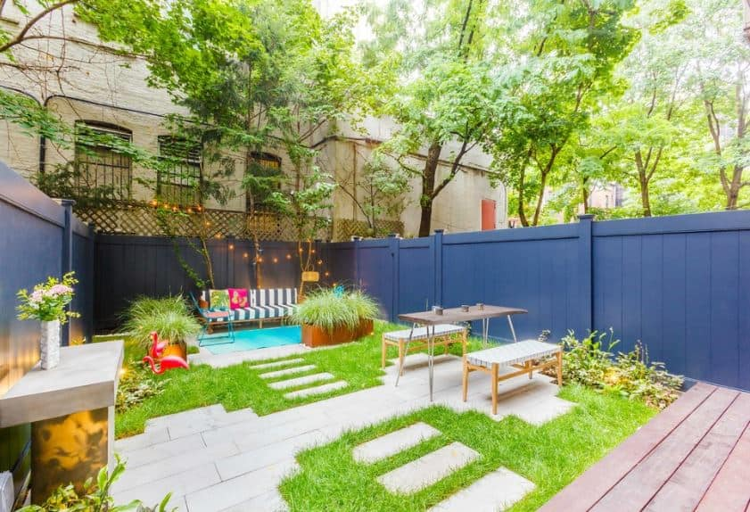 This small backyard of grass and stone walkways has a cooking area, an outdoor dining area with wooden benches flanking a wooden table and a lounge area with colorful benches, chairs and even rope lights accenting the blue wooden walls of this Scandinavian-Style landscape.
