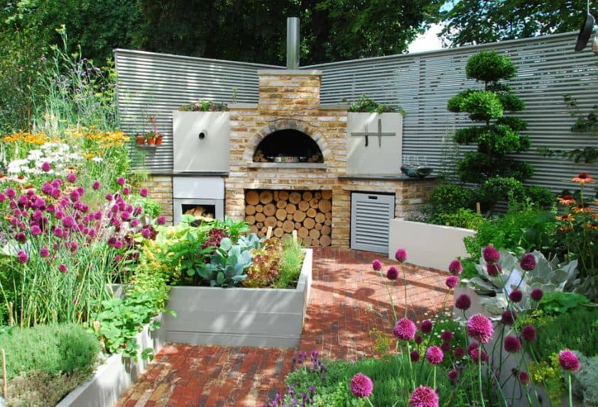This corner of the Scandinavian-Style landscape features a brick wall structure for a cooking area with dark countertops and a fireplace flanked with plants and a stack of firewood beneath. The brick flooring and walkway is surrounded by colorful plants.