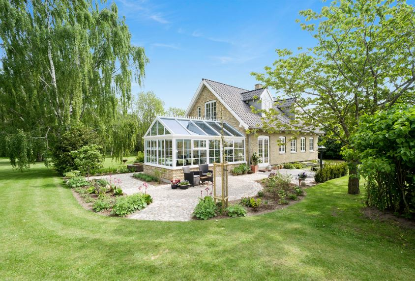 This house features a large room surrounded by glass windows and glass ceiling that is perfectly paired with a beautiful scenery of flowers, well-manicured grass carpet and a couple of tall trees that dwarf the house making it seems smaller.