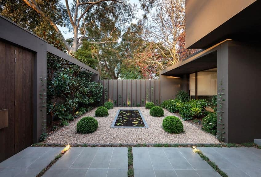 This Scandinavian-Style landscape has a tall gray wall with trees lining the sides to go up the trellis at the top of the wall. next to the wall is a gravelly lawn that has four mounds of shrub surrounding a rectangular koi pond with an infinity pool design.