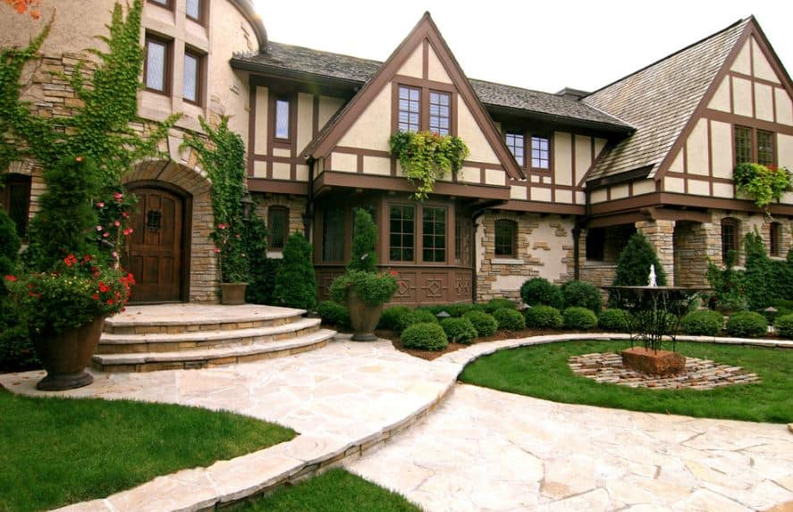 The wooden main door has a stone stairway that is flanked by potted flowering shrubs leading grassy carpets perfectly curved to follow the lay of the stone walkways. There's a dark iron fountain in the middle of this garden with a brick flooring.