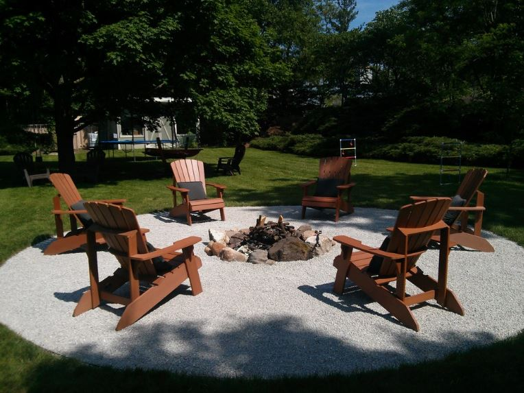 This grassy backyard has well-manicured lawns dominated by a large tree shading various lawn chairs beneath it. There is also a circular area with gravel flooring and an outdoor fireplace in the middle. Surrounding it are wooden lawn chairs for an impromptu fireside story.