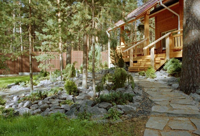 This charming wooden cottage is surrounded by a Scandinavian-Style landscape that complements the surrounding nature of tall pine trees and shrubbery. There is a stone walkway embedded into the soil leading from the wooden stairs of the house.