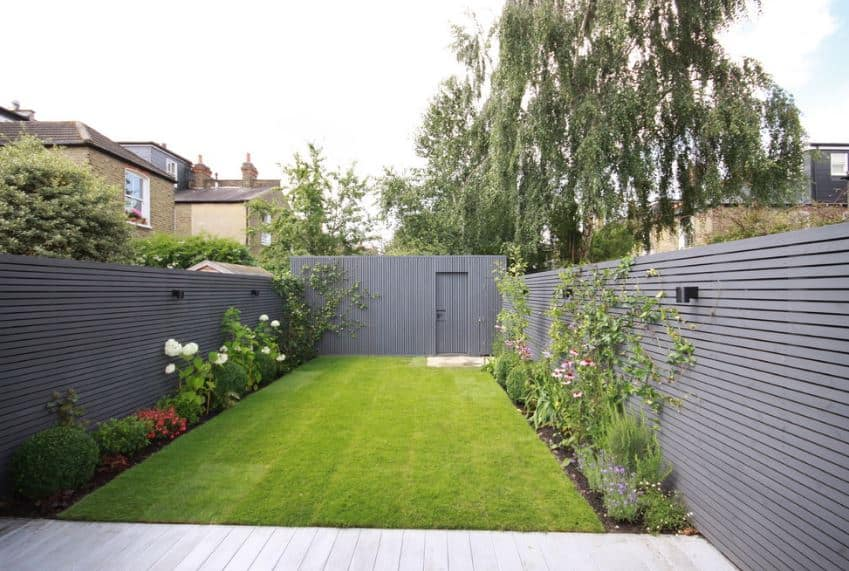 This is a small backyard with a well-manicured carpet of grass surrounded by various colorful flowering plants. A gray wooden fence borders this area together with the wooden shed at the end of the lawn with the same gray wooden design.