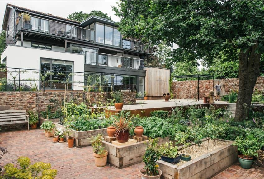 This modern house filled with glass walls and balconies is provided with a wonderful view of a vast garden at the front of the house. Before this garden is a wide and open area for outdoor parties that leads to a small stairway to the potted plants and brick floor of the garden.