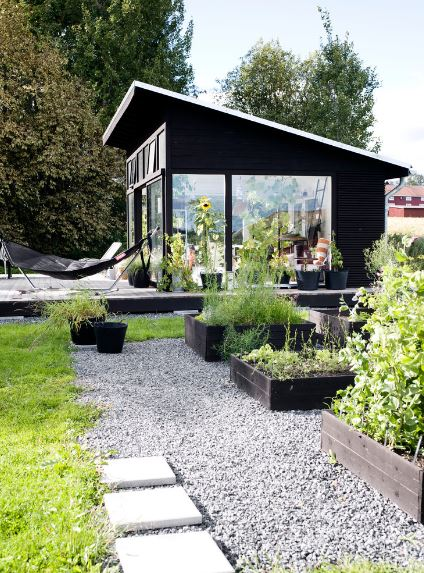 There is a comfortable hammock outside the glass walls of the small house for a relaxing afternoon next to potted plants. This is on a raised wooden platform next to the grass and gravel lawn that has squares of wooden soil beds for the plants and herbs.