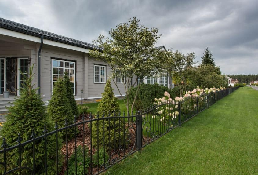 The side of the house is bordered with low dark iron fencing that has lovely intricate details. This is well contrasted by the white flowers on the other side of the fence together with pine trees and shrubs that line the side of the simple gray house.
