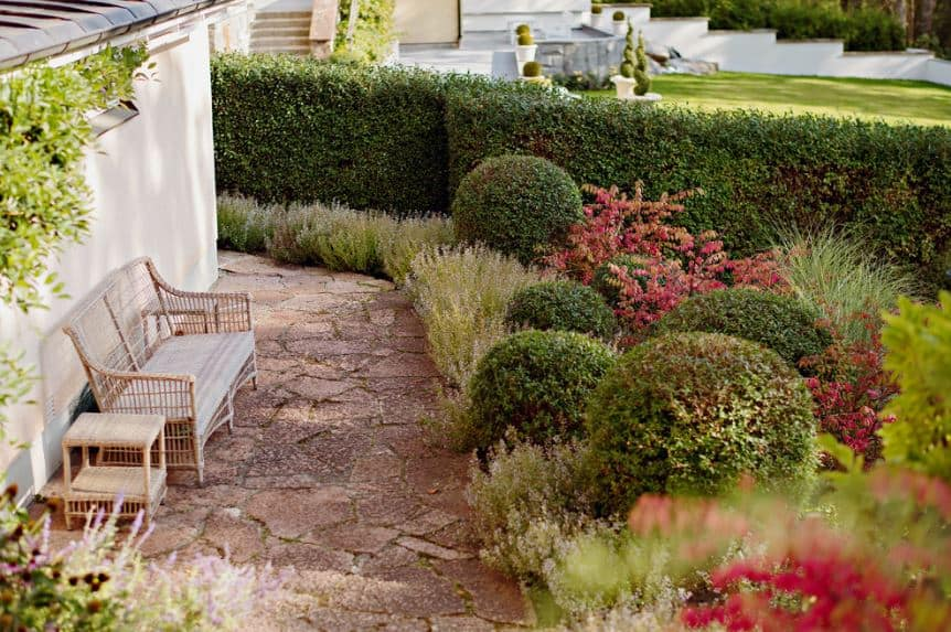 There is a stone walkway surrounding the white walls of the house paired with a rustic set of wooden bench and side tables for those who want to gaze upon the colorful shrubs of the garden that are manicured to have spherical shapes.