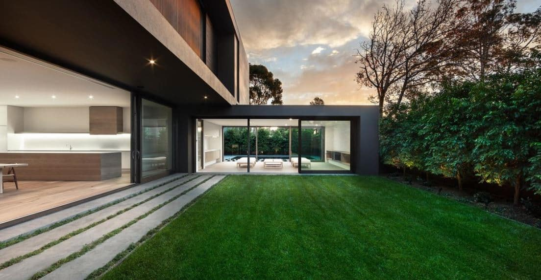 This lawn matches the simplicity and modern lines of the house in true Scandinavian-Style design. The side of the house has a set of glass doors that open to a simple well-manicured carpet of grass bordered with a row of medium-sized trees at the side.