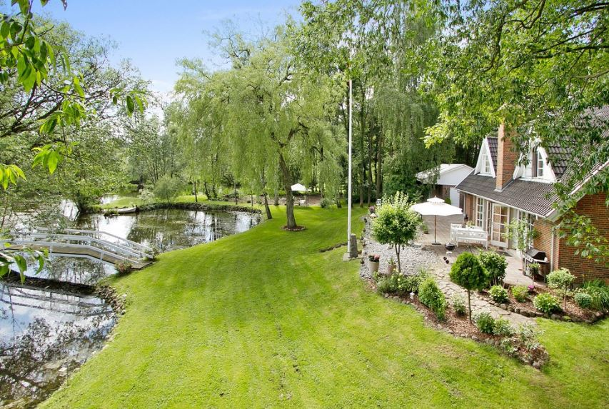 This lakeside house makes the most of its beautiful surroundings with a well-maintained grassy carpet leading to the lakeside that has a wooden bridge. Just outside the house is a wood-floored area for an outdoor dining experience with barbeque and trees.